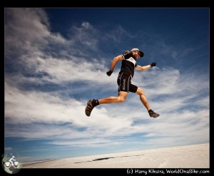Harry jumps in his Santos outfit, for joy on the Salar de Uyuni, on WorldOnaBike.com, from Alaska to Ushuaia on a bicycle